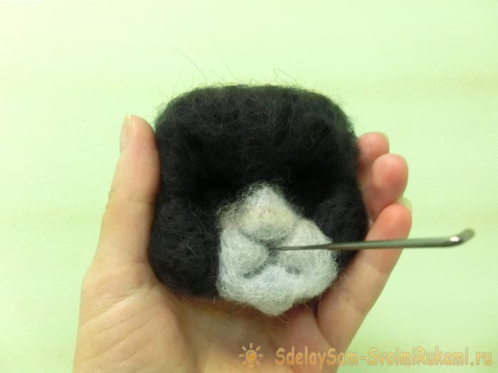 a spotted cat made of wool felting